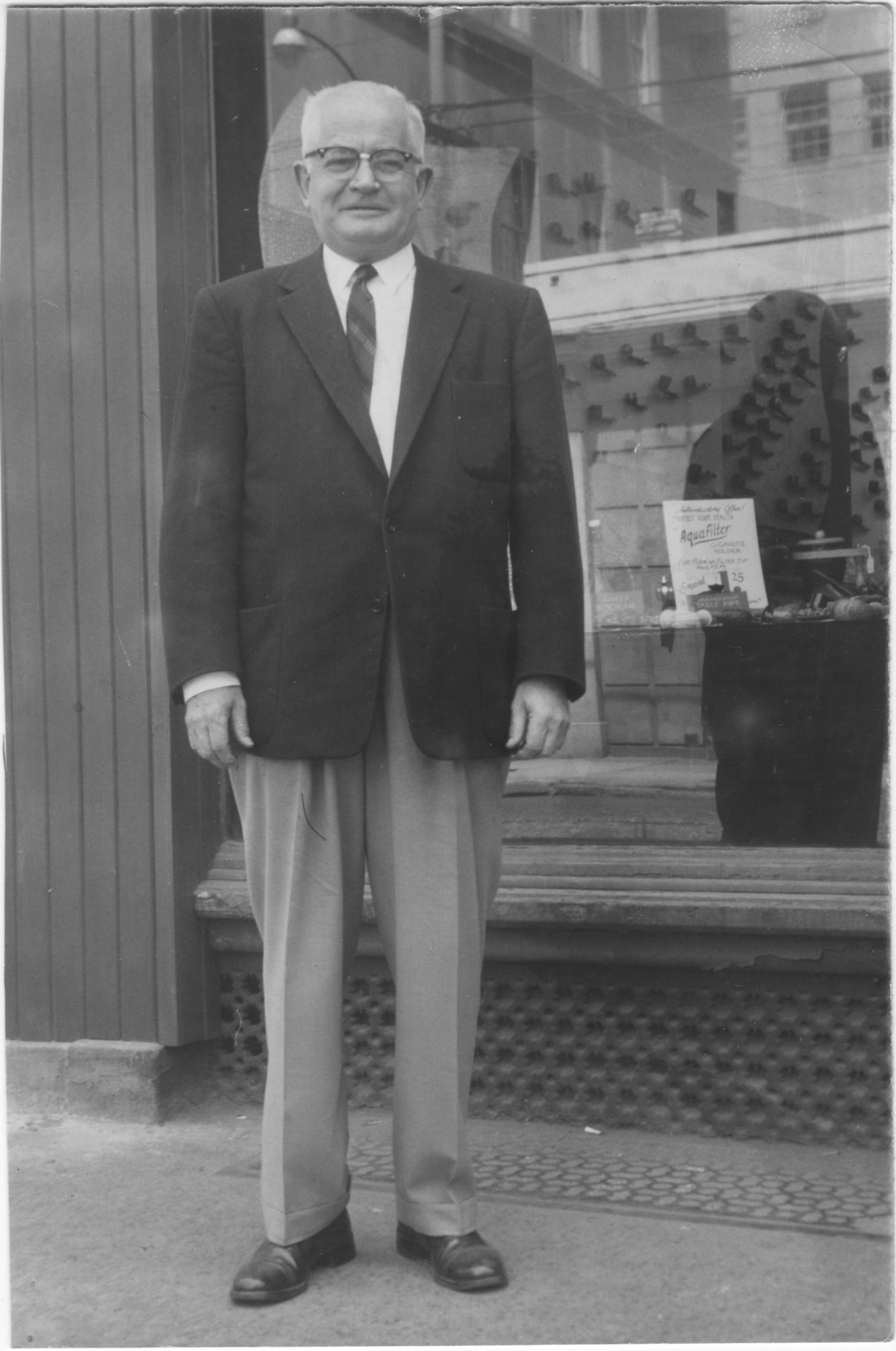 Photo of Harold Harber in front of Brigham's Pipe Store where he worked in the late 1950s (or early 1960s?)